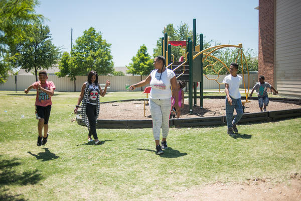 C'Artis Harris and her children run around a nearby Dallas playground.