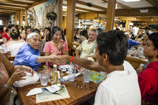 Sam Marsenison (foreground, in white shirt) and family gather in celebration at Puerto Sagua, a favorite Cuban restaurant in Miami Beach, on the eve of Sam's graduation.