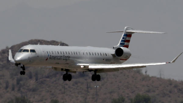 An American Eagle jet is seen through heat ripples as it lands at Phoenix Sky Harbor International Airport. American Airlines canceled dozens of regional flights there on Tuesday because of extreme heat.