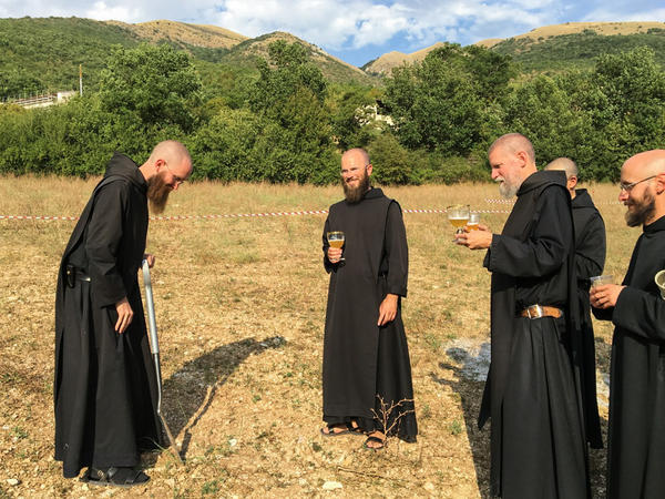 Father Benedict Nivakoff (left) blesses the land and lays the cornerstone of the new mountainside brewery while the other monks celebrate with Nursia beer.