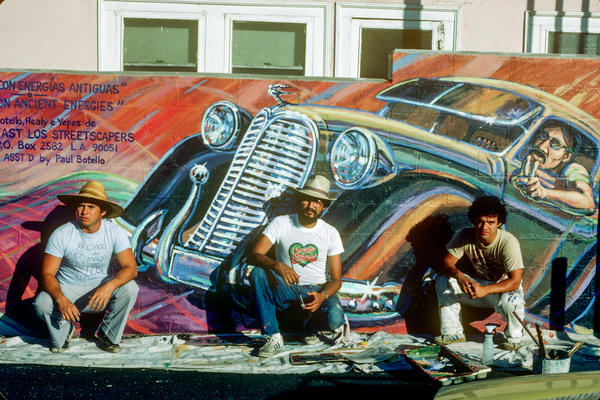 East Los Streetscapers David Botello (left), Wayne Healy and George Yepes were commissioned by Shell Oil to adorn a gas station wall in Boyle Heights. The resulting mural was called <em>Filling Up on Ancient Energies.</em>