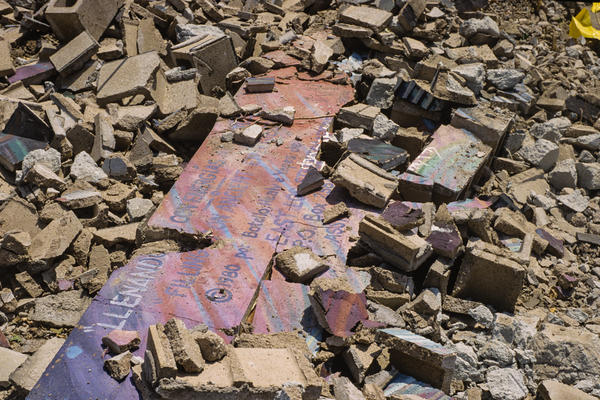 In 1988, <em>Filling Up on Ancient Energies </em>was mostly destroyed to make way for a parking lot. This fragment among the rubble bears East Los Streetscapers' copyright symbol.