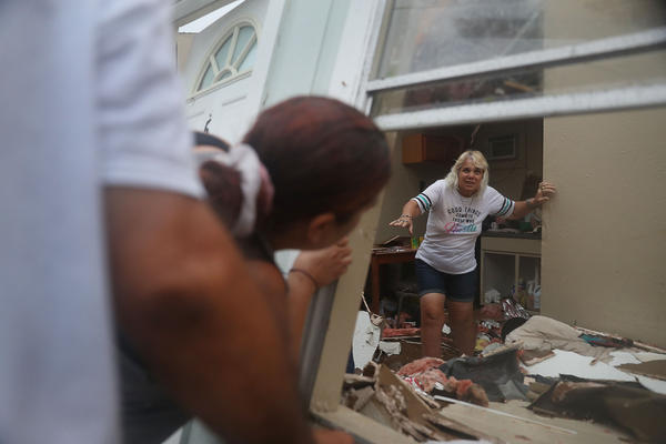 Donna Raney makes her way out of the wreckage of her home as Daisy Graham tells her she will help her out of the window after Hurricane Harvey destroyed the apartment in Rockport. Donna was hiding in the shower after the roof blew off and the walls of her home caved from the winds.