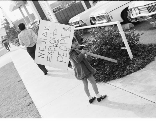 <em>Chicanita protesting unfair labor practices at Mejian Chevrolet Car Dealership, East L.A. </em>Circa 1972.<em> </em>