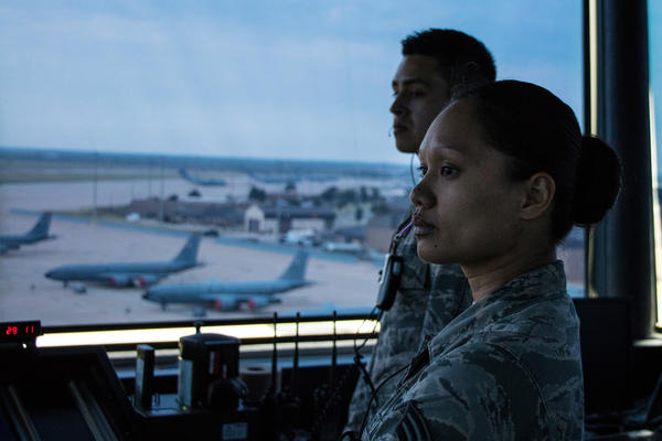 Senior Airman Yazmine Nanasca with a control tower crew at Altus Air Force Base guide a C-17 cargo plane a KC-135 tanker as it taxis to the runway for a day-long training mission in southwestern Oklahoma.