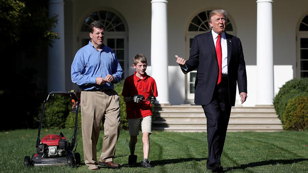 "Eleven-year-old Frank ""FX"" Giaccio walks with President Donald Trump while mowing the grass in the Rose Garden of the White House on Friday. Also pictured is Frank's father, Greg Giaccio."