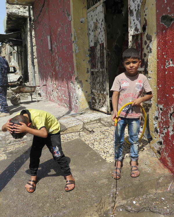 Children cool off on a destroyed street in the old city in west Mosul. There's no electricity or water but residents are starting to dig wells and trying to repair their damaged homes.