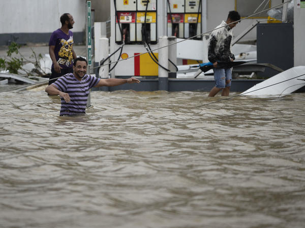 People walk next to a flooded gas station in Humacao, Puerto Rico on Wednesday.