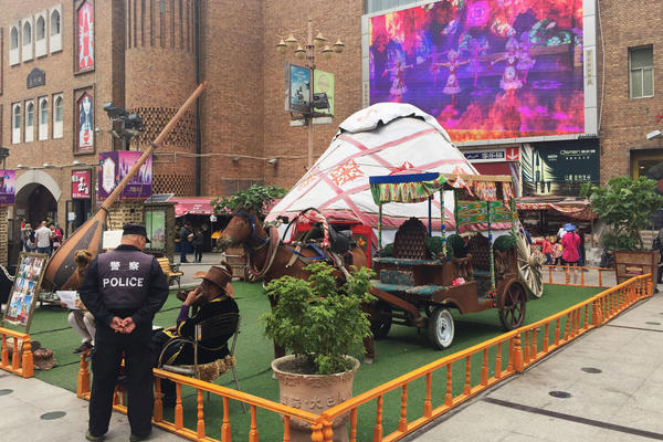 At Urumqi's Grand Bazaar, a police officer chats with a local vendor while a video promoting China's ethnic minorities plays on a big screen overlooking the square. This was the site of Uighur protests in 2009 that sparked citywide riots, leading to the death of hundreds. Since then, the city has become one of China's most tightly controlled police states.