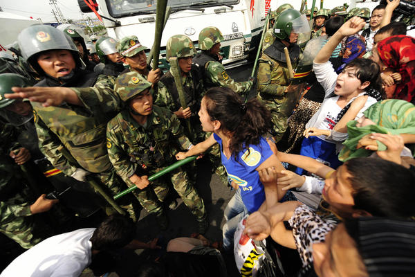 Ethnic Uighur women yell at Chinese riot police during a protest in Urumqi in China's far west Xinjiang region on July 7, 2009. Nearly 200 people were killed and more than 1,000 injured in riots throughout July 2009.