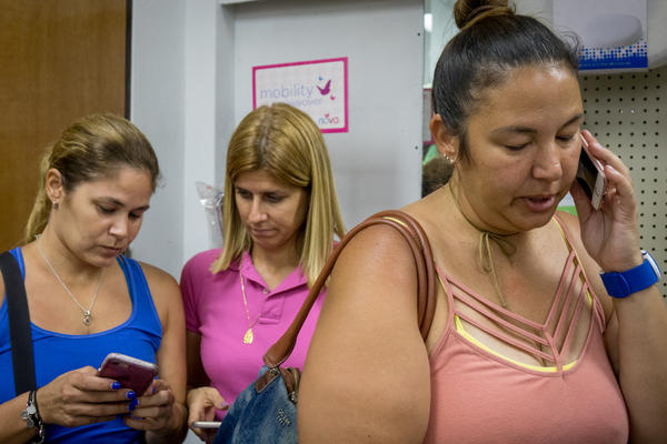 Marilee Dominguez (right) speaks on the phone with her sister-in-law in Costa Rica inside Derkes Pharmacy in Guayama, Puerto Rico. The owner of the store, Ana Rita Sued, (center) has made her phone with a satellite connection available to residents so they can contact relatives and friends outside of Puerto Rico.
