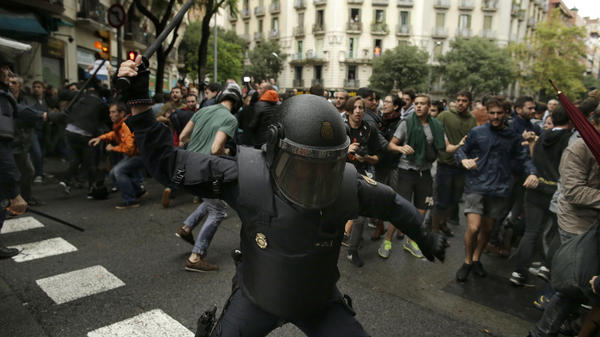 A Spanish riot police officer swings a club against would-be voters near a school assigned to be a polling station by the Catalan government in Barcelona, Spain on Sunday.