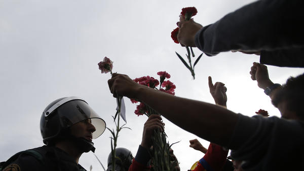 People try to offer flowers to a civil guard at the entrance of a sports center used as a polling station near Girona, Spain on Sunday.