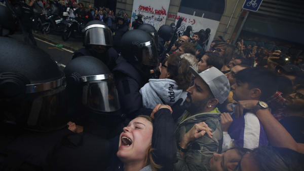 Spanish National Police push away referendum supporters outside a polling station in Barcelona, Spain on Sunday.