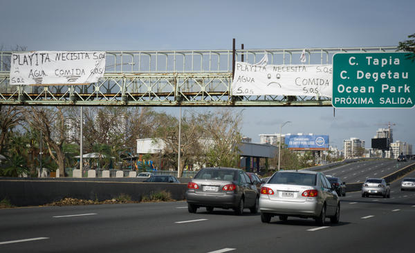 A pair of SOS signs hang from a pedestrian overpass in the San Juan's Playita neighborhood asking for food and water following Hurricane Maria's destruction in Puerto Rico.