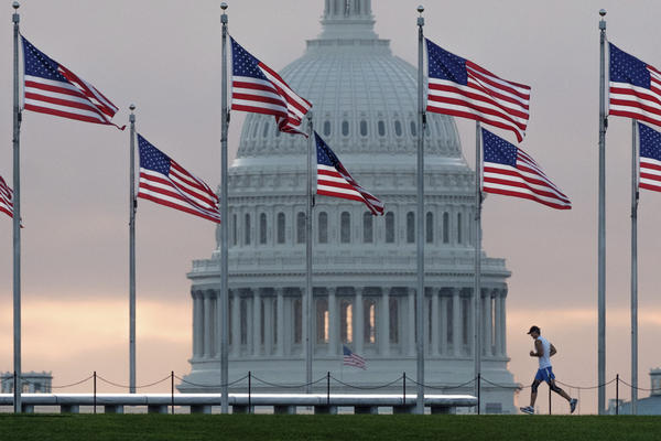 A early morning runner crosses in front of the U.S. Capitol as he passes the flags circling the Washington Monument, Wednesday, Sept. 27, 2017.