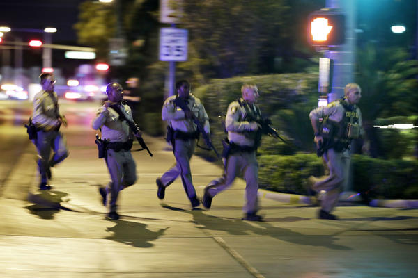 Police run to cover at the scene of a shooting near the Mandalay Bay resort and casino on the Las Vegas Strip, Sunday, Oct. 1, 2017, in Las Vegas. Multiple victims were being transported to hospitals after a shooting late Sunday at a music festival on the Las Vegas Strip. (John Locher/AP)
