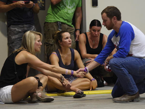 People hold hands in prayer while hiding inside an airplane hangar after a mass shooting in which dozens were killed at the Route 91 Harvest Festival in Las Vegas.