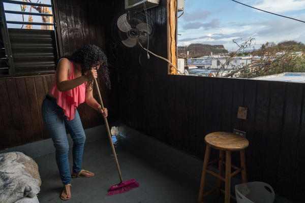 Liz Vazquez Ojeda sweeps water from a rain shower on the floor. The roof was destroyed during the hurricane.