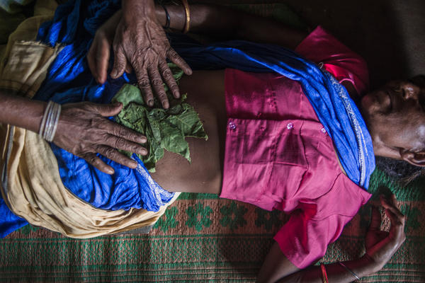 In India, a traditional midwife attempts to induce abortion by massaging herbs and oil on a woman's belly.