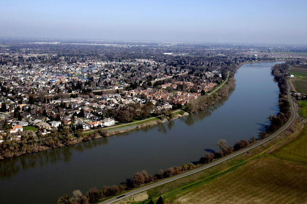 Houses are seen along the Sacramento River. Sacramento doesn't have hurricanes to worry about. Instead, it's the huge winter storms that hit the Sierra Nevada that can trigger a flood event in the area.