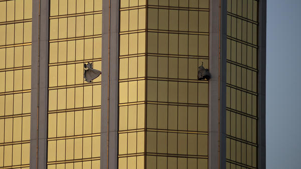 In this photograph taken the morning after the shooting, drapes billow out of broken windows at Mandalay Bay in Las Vegas. Officials say Stephen Craig Paddock had an unobstructed view to rain gunfire on the crowd at the Route 91 Harvest music festival Sunday night.