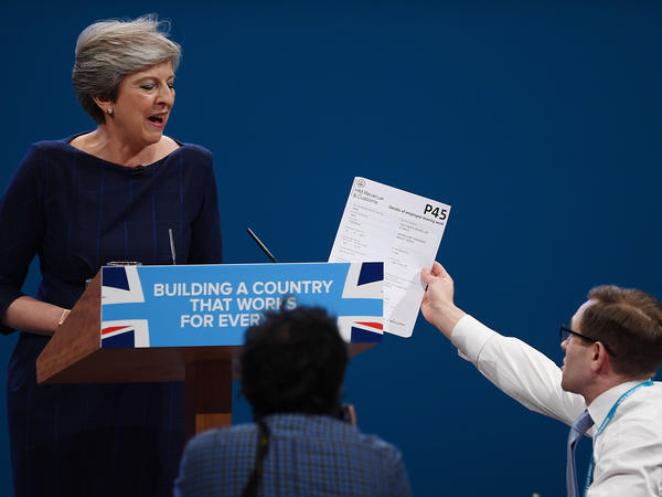 Comedian Simon Brodkin, also known as Lee Nelson, hands Prime Minister Theresa May a P45 form — the equivalent of a pink slip — during her speech at the Conservative Party Conference in Manchester.