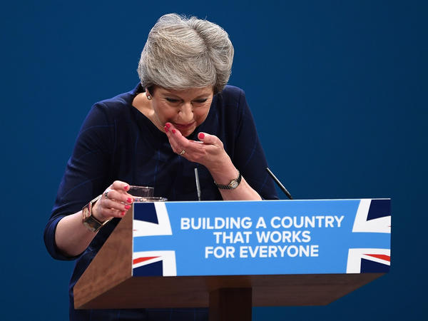 May takes a cough drop during her keynote speech to delegates and party members on the last day of the Conservative Party Conference in Manchester.