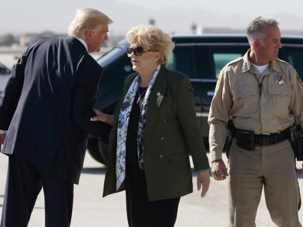 President Trump talks with Las Vegas Mayor Carolyn Goodman and Clark County Sheriff Joseph Lombardo (right) after arriving at Las Vegas McCarran International Airport on Wednesday to meet with victims and first responders of the mass shooting.