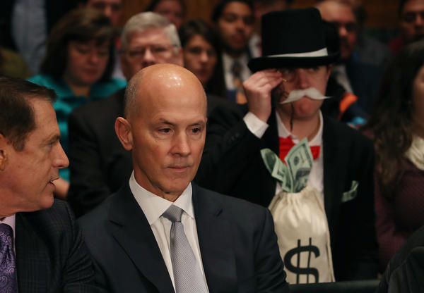 As former Equifax CEO Richard Smith prepares to testify before the Senate Banking Committee on Capitol Hill on Wednesday, activist Amanda Werner looks on through a monocle.