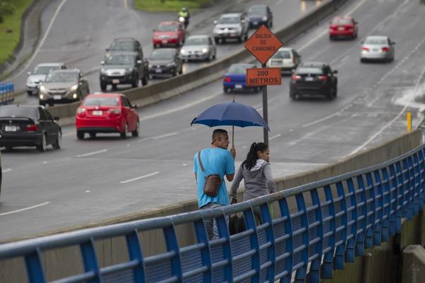 A couple cross a bridge over the Maria Aguilar river on the outskirts of San Jose, Costa Rica, Thursday, Oct. 5, 2017. Tropical Storm Nate formed off the coast of Nicaragua on Thursday and was being blamed for at least 17 deaths in Central America as it spun north toward a potential landfall on the U.S. Gulf Coast as a hurricane over the weekend. (Moises Castillo/AP)