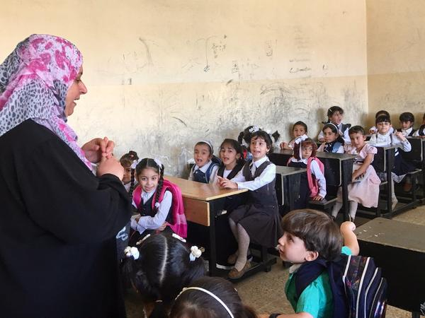 A teacher greets students on the first day of elementary school in Mosul, where regular classes have started for the first time since ISIS took over the northern Iraqi city three years ago. Hundreds of schools were damaged or destroyed in the fighting to take back Mosul. Others that have reopened lack books and basic supplies.