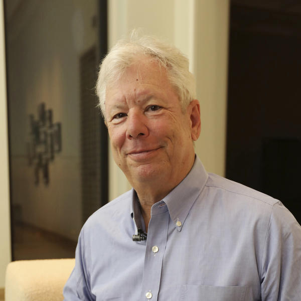 In this photo provided by the University of Chicago, Richard Thaler poses for a photo with his books at his home in Chicago after winning the Nobel prize in economics, on Monday.