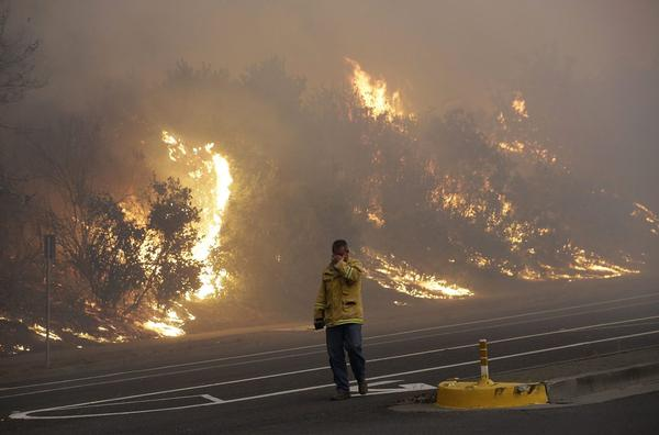 A firefighter covers his eyes as he walks past a burning hillside in Santa Rosa, Calif., Monday, Oct. 9, 2017. Wildfires whipped by powerful winds swept through Northern California, sending residents on a headlong flight to safety through smoke and flames as homes burned. (Jeff Chiu/AP)