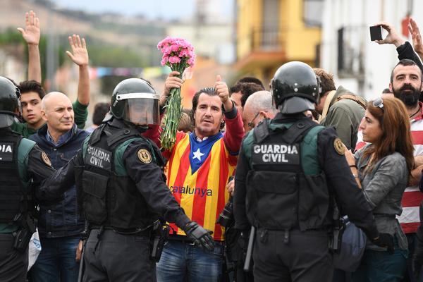 A man dressed in the Catalonian flag gives the thumbs up as police move in on the crowds gathered outside to prevent the police from stopping the voting on a referendum on Catalonia's independence from Spain. The Spanish government in Madrid declared the vote illegal and undemocratic.