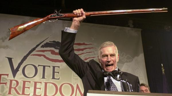 """The late Charlton Heston, the former actor and head of the National Rifle Association, addresses gun owners during a """"get-out-the-vote"""" rally in New Hampshire in October 2002."""