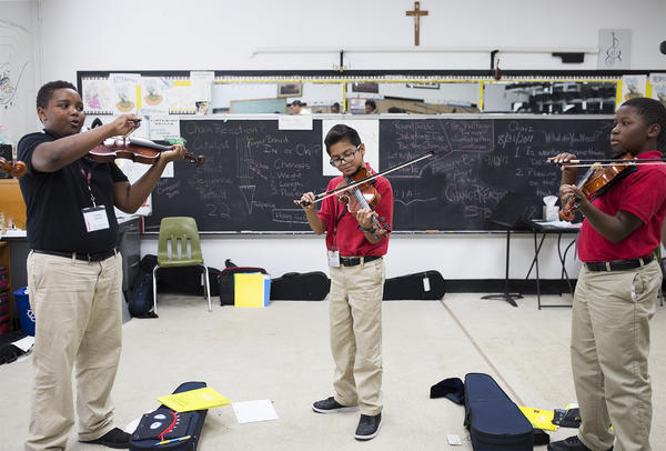 Students get ready for a violin class taught by Philip Tinge at Sister Thea Bowman Catholic School in East St. Louis. Most students at the school come from low-income families, and would get first priority on tax credit scholarships.