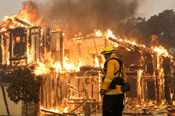 A firefighter monitors a house burning in Santa Rosa. Wildfires whipped by powerful winds swept through Northern California, sending residents on a headlong flight to safety through smoke and flames as homes burned.