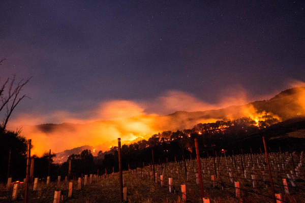 Fire glows on a hillside in Napa on Monday night as multiple wind-driven fires continue to whip through the region.