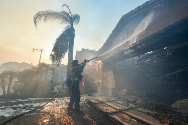 A fireman puts out a fire at a home in Anaheim after a fire spread quickly through the area destroying homes, prompting mandatory evacuations and freeway closures.