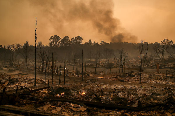 Smoke billows from a neighborhood that was destroyed by a fast moving wild fire on Monday in Santa Rosa, Calif. Ten people have died in wildfires that have burned tens of thousands of acres and destroyed over 1,500 homes and businesses in several Northern California counties.