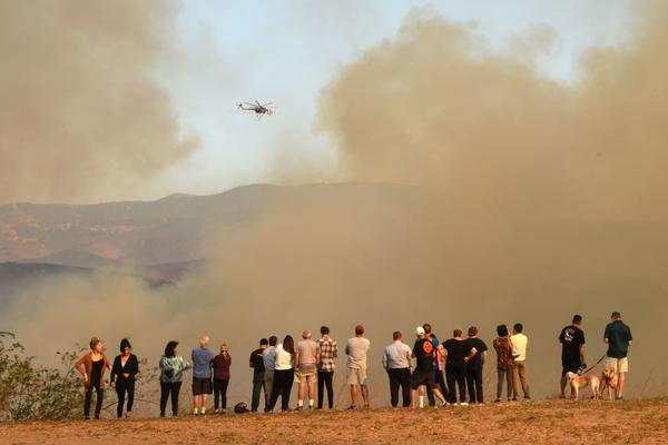 People watch water-dropping helicopters amidst smoke from the Canyon Fire 2 in Orange.
