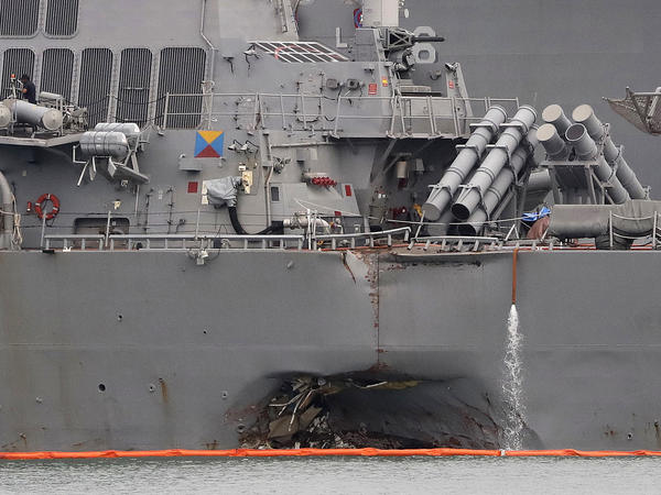 The USS John S. McCain, shown docked in Singapore on Aug. 22, was damaged after colliding with an oil tanker. Two top U.S. Navy officers were dismissed Tuesday as the 7th Fleet continues its investigation into the crash.