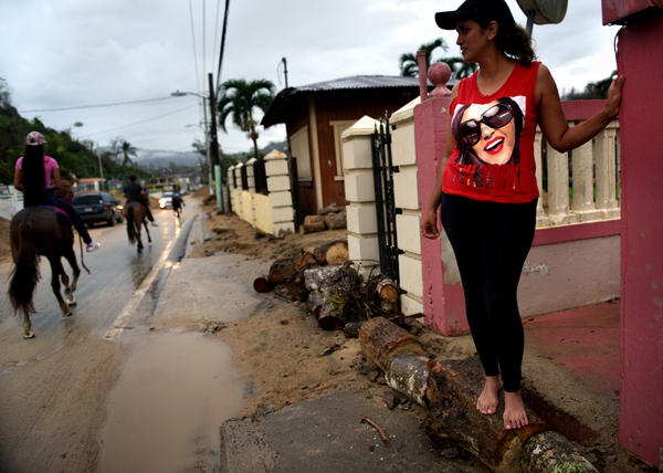 Residents handle aftermath of hurricane with resilience, humor and spirit. Jaylyn Rosario stands on makeshift barrier to prevent flooding of her home on Avenida Esteves, piled high with sand and debris washed in from a creek.