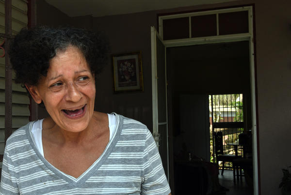 "Daly Montavo, born in Puerto Rico and raised in New York City, laughs at her home on Avenida Esteves after filling jugs of water from a National Guard delivery to the neighborhood. She says, ""We're here and that's all that matters."""