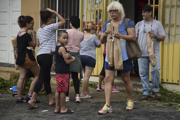 People buy bread at Ortiz bakery after the passing of Hurricane Maria, in Yabucoa, Puerto Rico, Thursday, September 21, 2017.