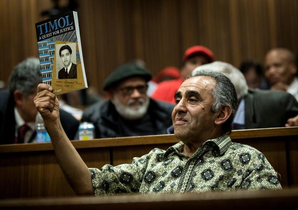 "Former anti-apartheid activist Mohamed Timol, brother of the late Ahmed Timol, holds up a copy of the book ""Timol: A Quest for Justice"" at the judgment proceedings in Pretoria on Thursday."