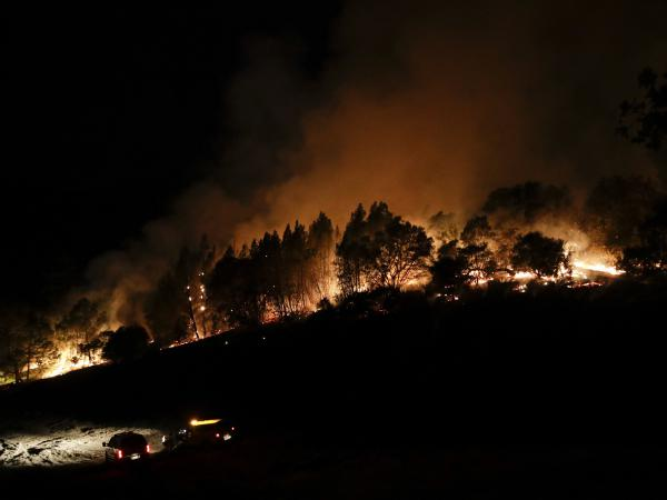 Firefighters watch from their fire trucks as wildfires continue to burn on Thursday, near Calistoga, Calif.