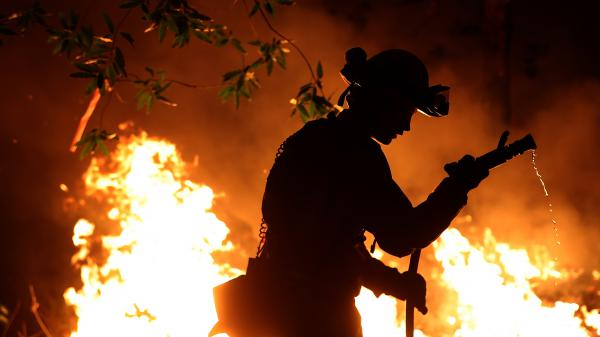 Cal Fire firefighter Trevor Smith battles the Tubbs Fire near Calistoga, Calif., on Thursday. Wildfires in Northern California have killed dozens of people and destroyed thousands of homes and businesses.