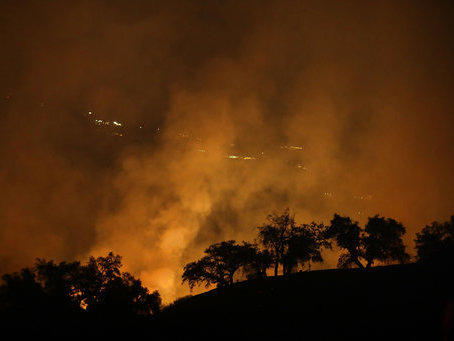 The orange glow of one of California's many wildfires can be seen Friday from a hilltop in Geyserville, Calif.